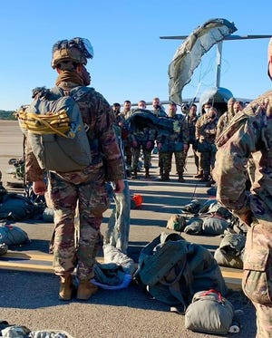Paratroopers with the 1st Brigade Combat Team, 82nd Airborne Division receive a pre-jump demonstration on the function of the T-11 reserve parachute while waiting to board a C-17 Globemaster on Dec. 8 at Pope Army Airfield before conducting a joint forcible entry during Operation Devil Storm at Fort Bragg.