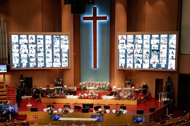 Umat Kristen di layar menghadiri kebaktian Natal online untuk menjaga jarak sosial dan pencegahan terhadap virus corona di Gereja Injil Penuh Yoido di Seoul, Korea Selatan, Jumat.