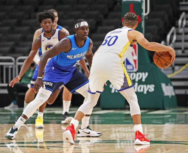 Bucks guard Jrue Holiday defends against Warriors guard Stephen Curry  on Friday.