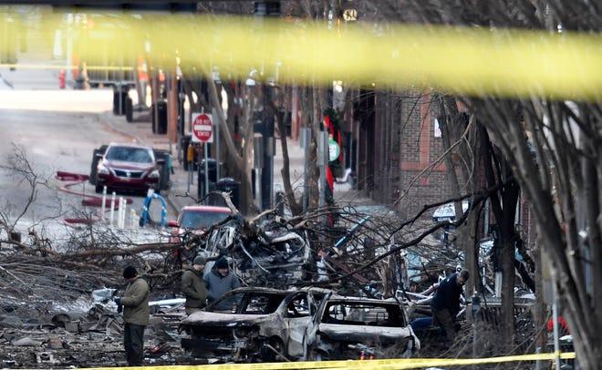 Investigators walk through the scene of the explosion on Second Avenue on Friday, Dec. 25, 2020 in Nashville, Tenn.