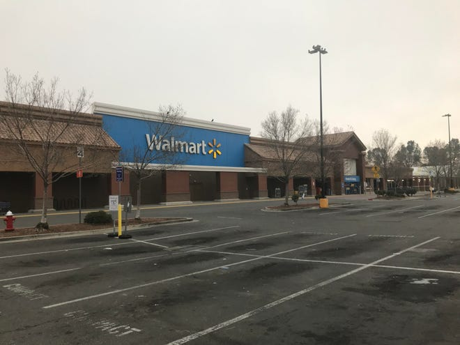 The parking lot at the Redding Walmart is empty on Friday, Dec. 25, 2020, as the store was temporarily closed. Police said a driver crashed through the front of the store and drove around the cashiers' area on Thursday evening. The vehicle matched the description from an earlier carjacking. An officer later shot and killed a female suspect. The Walmart had reopened by Saturday, Dec. 26, 2020.