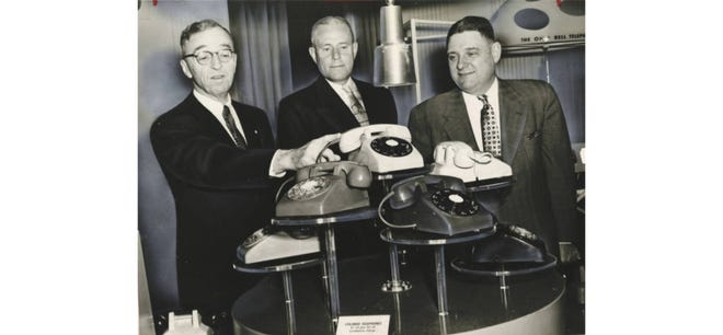 """Ohio Bell President John Greene, Akron Division Commercial Manager W.W. Osmer and Vice President and General Manager K.L. Ervin admire colorful phones in January 1955 at the Mayflower Hotel in downtown Akron. If it hadn't been a black-and-white photo, you would see such """"harmonizing colors"""" as ivory, green, beige, brown, red, yellow, gray and blue."""
