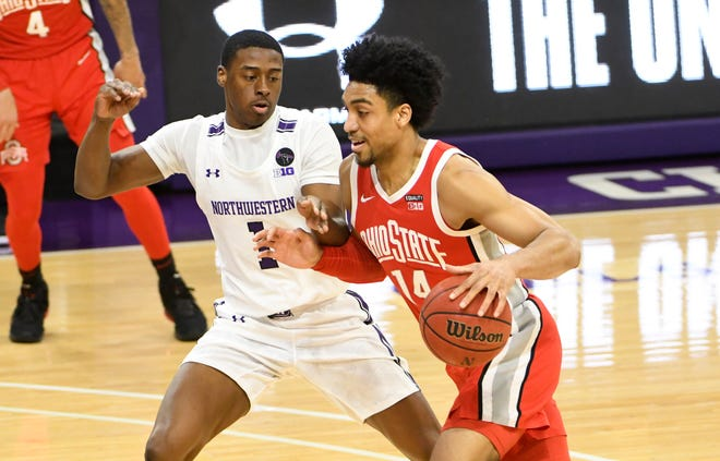 Ohio State's Justice Sueing drives against Northwestern's Chase Audige.