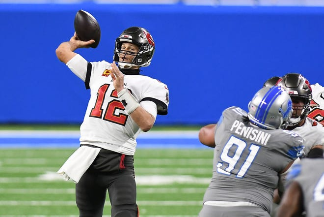 Tom Brady threw four touchdown passes, and the Buccaneers went on to rout the Lions on Saturday, clinching a playoff spot for the first time since 2007.