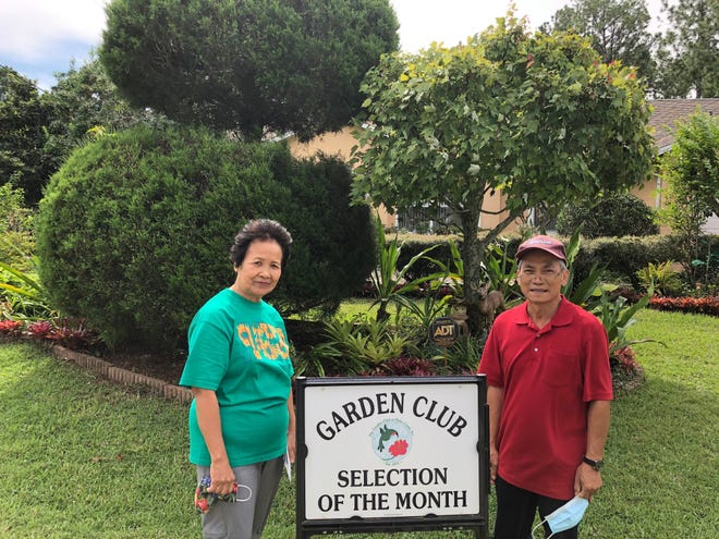 Benita and Rey Mayo stand in front of their award-winning landscaping.