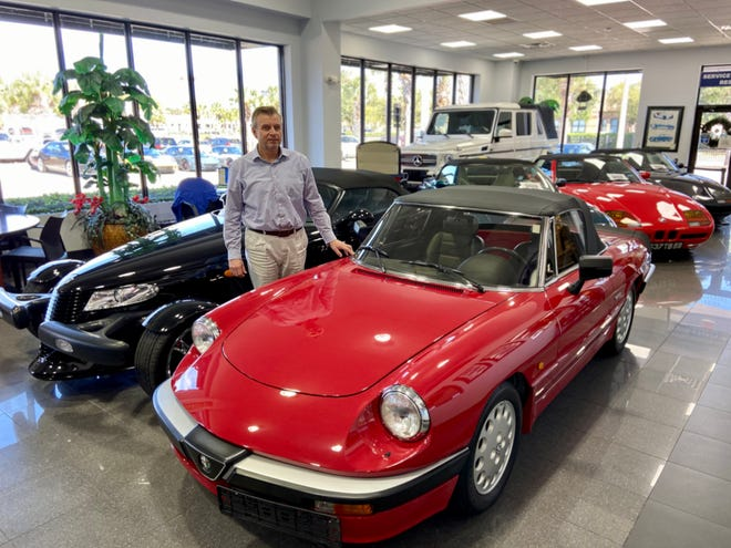 Jake Sydorowicz's Collector Series at World Imports USA includes hard-to-find, low-mileage imports and American models. On the right is a 1987 Alfa Romeo Spider 2.0 Quadrifoglio Verde with only 2,884 miles. Behind Sydorowicz is a 2000 Plymouth Prowler with only 2,567 miles.