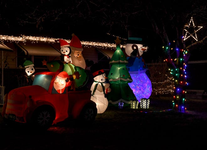 A variety of inflateable Christmas decorations fill a front yard as well as lights on trees and the house at a residence in the 2500 block of North Sixth Street. [BRAD NADING/GARDEN CITY TELEGRAM]