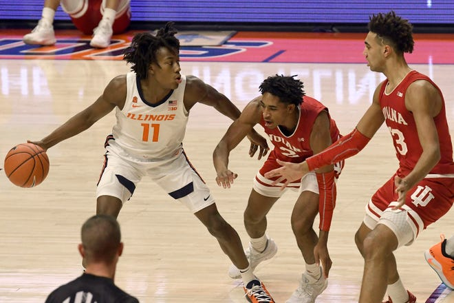 Illinois guard Ayo Dosunmu (11) is pressured by Indiana's guard Armaan Franklin (2) and forward Trayce Jackson-Davis (23) in the first half of an NCAA college basketball game Saturday, Dec. 26, 2020, in Champaign, Ill. (AP Photo/Holly Hart)