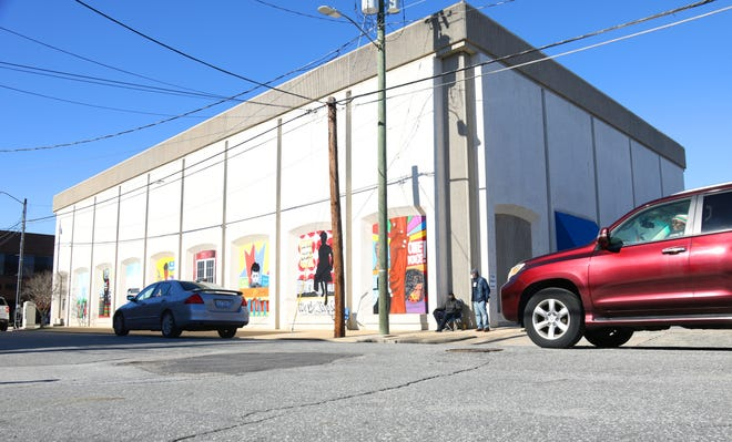 Cars pass by the Adkin High School Walkout Mural Saturday, Dec. 26, as drivers view the murals painted on the side of the Lenoir County Register of Deeds building on Caswell Street by artists Maximillian Mozingo and Jamil Burton.