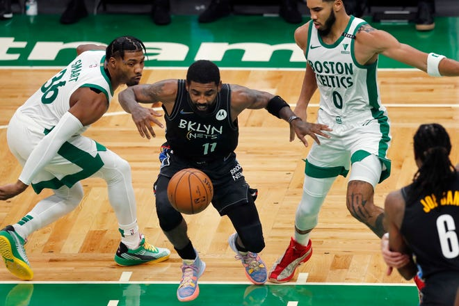 Nets point guard Kyrie Irving (middle) loses control of the ball against Celtics guard Marcus Smart (left) and Jayson Tatum during the first half of Brooklyn's 123-95 win over Boston on Christmas.