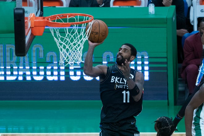 Dec 25, 2020; Boston, Massachusetts, USA; Brooklyn Nets point guard Kyrie Irving (11) shoots a layup during the fourth quarter against the Boston Celtics at TD Garden. Mandatory Credit: Gregory Fisher-USA TODAY Sports