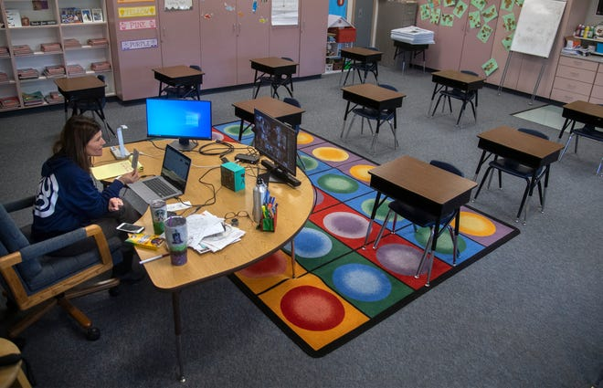 """First-grade teacher Gina Hughes leads an online virtual class from her classroom at Joshua Cowell Elementary School in Manteca. """"I have kids that ask if when the corona is over if they can give me a hug,"""" she said, """"and it literally brings me to tears."""""""