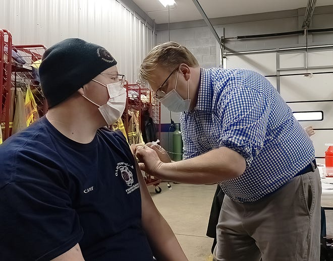 Garrettsville Fire Cadet Gavin Friess receives the Moderna vaccine against COVID-19 from Community EMS Paramedic Russell Hockenbrouch Saturday morning. Hockenbrouch received instruction from Portage County Health Department personnel on how to administer the vaccine.