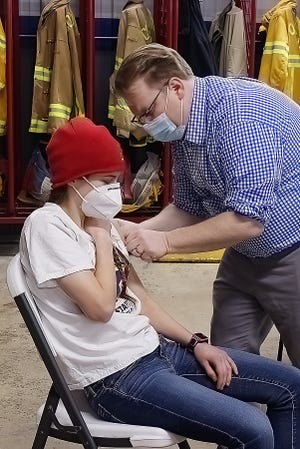 Community EMS Paramedic Russell Hockenbrouch delivers the vaccine to Kalli Barrett, an EMT with the WIndham Fire Department.