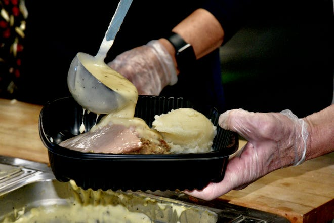 Kitchen volunteers add gravy to one of the turkey dinners given away at the 38th annual Bill Fekas Family Christmas Dinner held at the 4-H Building on Friday.