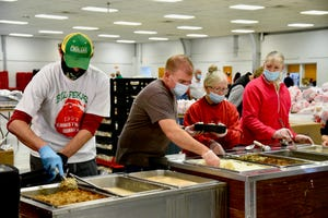 Volunteers prepare to-go meals during the Bill Fekas Family Christmas Dinner on Christmas Day in the 4-H building.