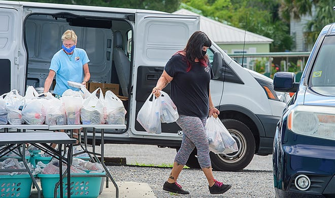 Pie in the Sky volunteer Rosalie Cocci takes bags of food to the car of a volunteer who will distribute it to elderly people in need in St. Johns County on Wednesday, June 17, 2020.