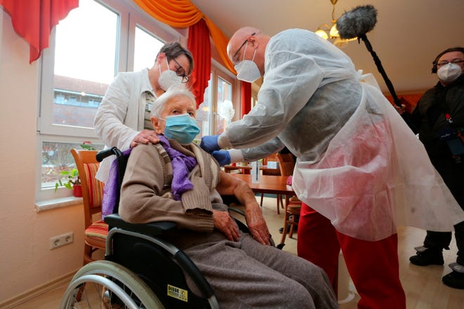 Doctor Bernhard Ellendt, right, injects the COVID-19 vaccine to nursing home resident Edith Kwoizalla, 101, Saturday in Halberstadt, Germany.