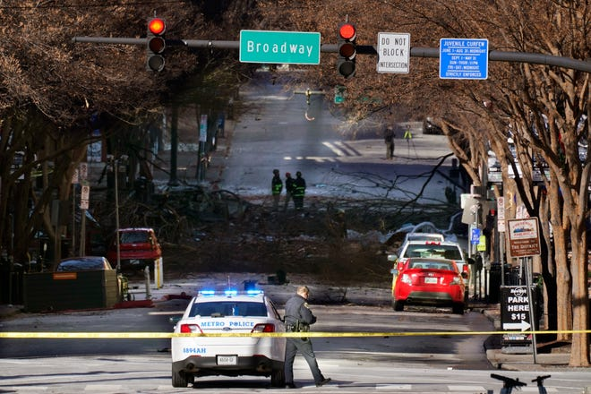 A Nashville Police officer blocks the entrance to the scene of an explosion Saturday in Nashville, Tenn.
