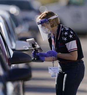 In this Nov. 3  photo, an election worker instructs a voter at a drive-through polling location in Kansas City, Mo.