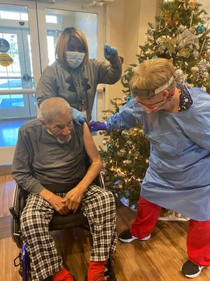 A veteran patient at the Fayetteville Veterans Affairs Coastal Health Care System's community living center in Fayetteville receives the COVID-19 vaccine.