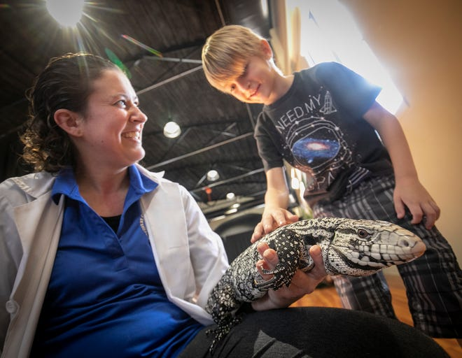 """Exhibit Coordinator and Animal Husbandry Director Celina Bazinte holds an Argentine Tegu named Eragon as Aiden Gee, 6, feels his back at the """"Eco Invaders"""" exhibit that was at the Discovery Center in Ocala from January to March in 2019."""