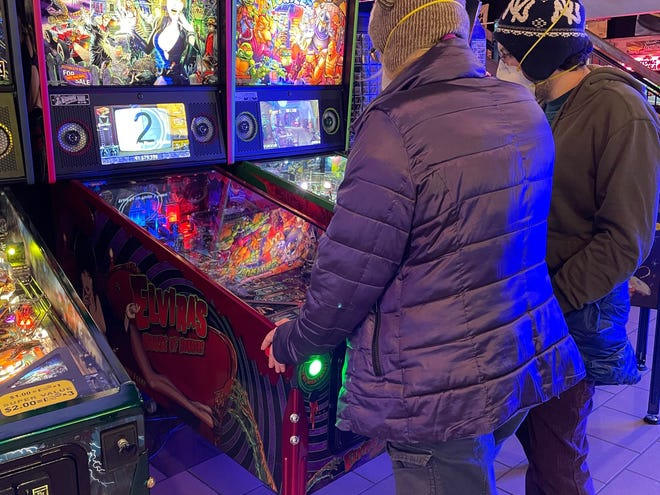 Customers play an arcade game at Pinball Pete's in Ann Arbor on Dec. 26 2020.