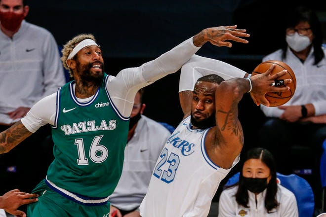 LeBron James, right,  looks to pass while under pressure from James Johnson during the first half of Friday's game in Los Angeles.