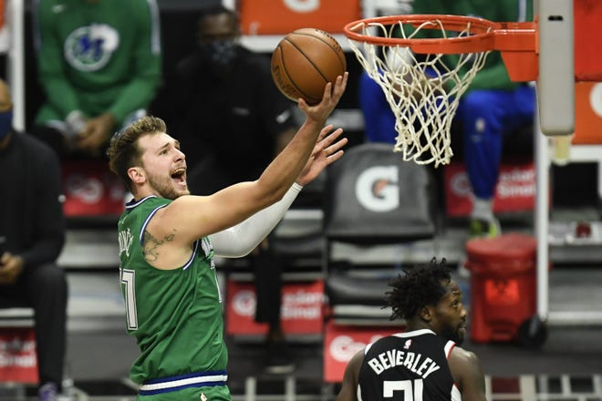 Dallas Mavericks guard Luka Doncic goes up for a basket past Los Angeles Clippers guard Patrick Beverley during the Mavericks 124-73 win Sunday in Los Angeles. Dallas set a modern-day record with a 50-point halftime lead.