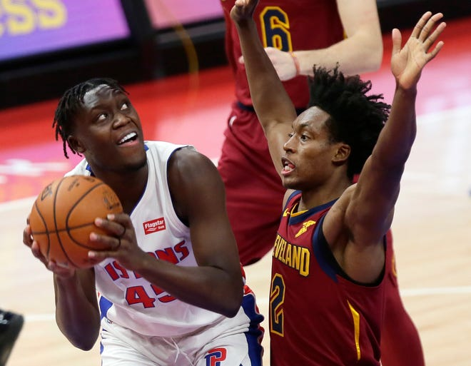 Detroit Pistons forward Sekou Doumbouya, left, is guarded by Cleveland Cavaliers guard Collin Sexton, right, during the first half of an NBA basketball game Saturday, Dec. 26, 2020, in Detroit. (AP Photo/Duane Burleson)