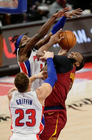Detroit Pistons forward Jerami Grant, left, tries to block a shot by Cavaliers center Andre Drummond, right, with forward Blake Griffin (23) helping defend during the second half of the Cavs' 128-119 double-overtime win Saturday in Detroit. [Duane Burleson/Associated Press]