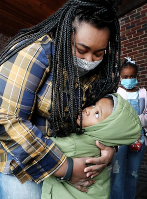 Lauren Marsh hugs Danari Bitting, 2, after giving him a bag of Christmas candy following a service at New Millennium Baptist Church on Sunday in Akron.