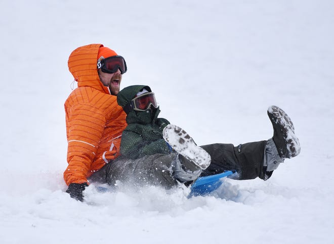 Andrew Anderson sleds with his son, Abram Anderson, 4, Saturday afternoon at Old Economy Park in Harmony Township.