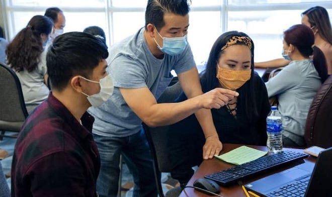 Problems still linger despite the Oklahoma Employment Security Commission's efforts to address them. Here, translator Calvin Nguyen, center, helps a client with the unemployment filing process in July during an unemployment filing event in Midwest City.