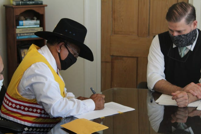 Chief August Creppel and lawyer Derrick Prentice sign documents for the new tribal office.