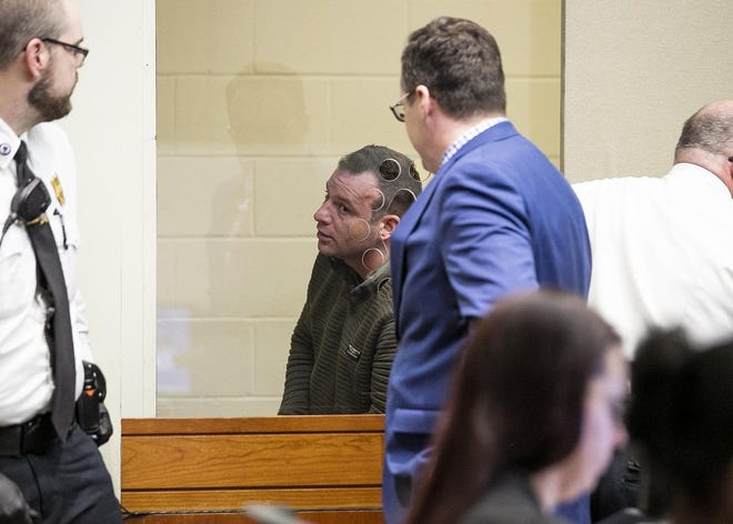 Bridgewater State University professor Nicholas R. Pirelli, 36, of Plymouth, center, speaks to his attorney, Scott Bradley, center-right, as he is arraigned on new charges of trafficking of a person for sexual servitude, distributing obscene matter, sexual conduct for a fee and criminal harassment at Brockton District Court on Wednesday, March 11, 2020.