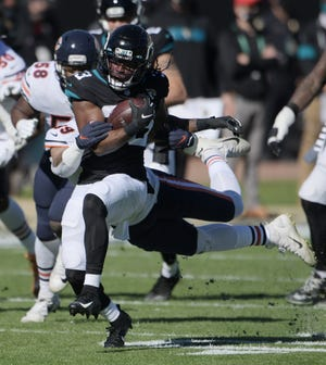 Jaguars running back Dare Ogunbowale (33) scrambles for yardage during first quarter action of Sunday's loss to the Bears.