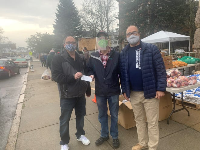 Philippe Gregoire, Director of St. Anne's Food Pantry accepts a donation from Barry Ferreira and Joseph Borges, co-chairs of the Prince Henry Society Humanitarian Committee.