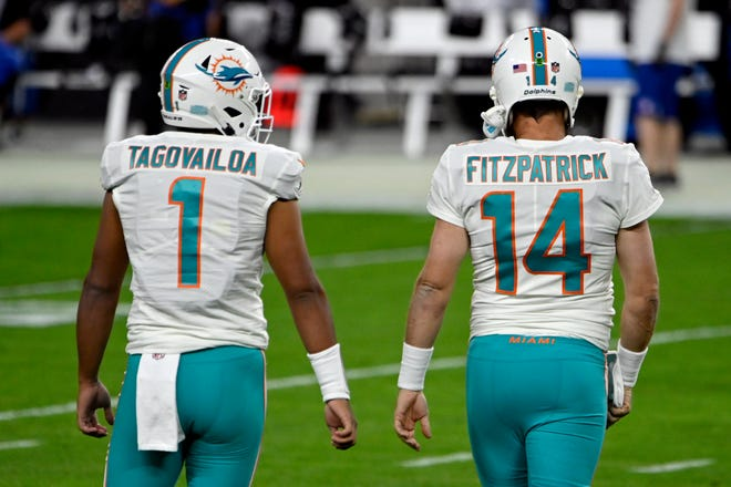 Dolphins quarterbacks Tua Tagovailoa (1) and quarterback Ryan Fitzpatrick (14) walk together during warm ups before Saturday's game against the Raiders. Despite a comeback led by Fitzpatrick, Tagovailoa remains the starter.