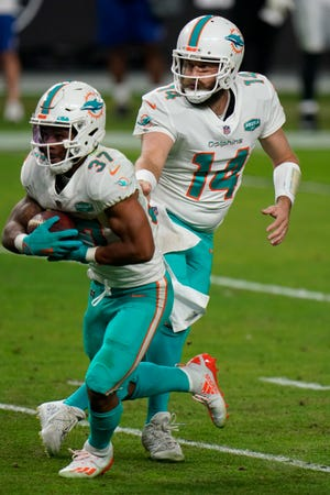 Dolphins quarterback Ryan Fitzpatrick hands off to running back Myles Gaskin  during the fourth quarter Saturday against the Las Vegas Raiders.