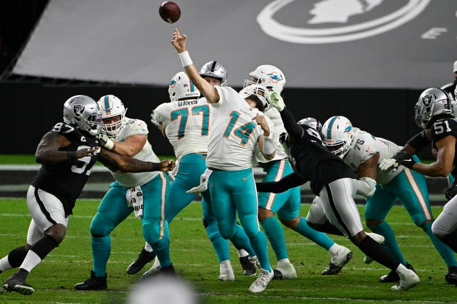 Las Vegas Raiders defensive end Arden Key (99) commits a roughing the passer penalty on Miami Dolphins quarterback Ryan Fitzpatrick (14) during the second half of an NFL football game, Saturday, Dec. 26, 2020, in Las Vegas. (AP Photo/David Becker)
