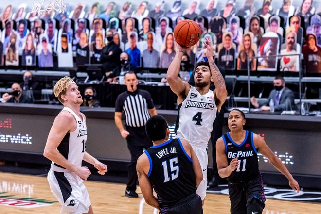 Providence's Jared Bynum (4) goes up for a shot over DePaul's Oscar Lopez Jr. (15) in the first half Sunday at Alumni Hall.