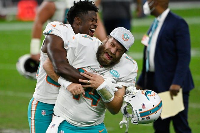 Dolphins wide receiver Isaiah Ford, left, celebrates with quarterback Ryan Fitzpatrick after defeating the Raiders, Saturday, Dec. 26, 2020, in Las Vegas. (AP Photo/David Becker)