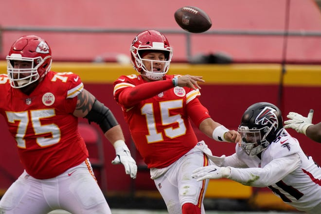 Kansas City Chiefs quarterback Patrick Mahomes  (15) throws a pass while being chased down by Atlanta Falcons Jacob Tuioti-Mariner during Sunday's game in Kansas City. (AP Photo/Charlie Riedel)