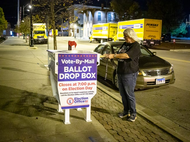 Debbie Johnson is the last person to cast a vote in the secure ballot drop box outside the Sangamon County Complex in Springfield with 10 minutes until the 7 p.m. deadline on Election Day on Nov. 3, 2020.