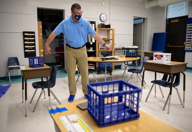 Jason Wind, Director of School Support for District 186, uses a tape measure to check the distance between desks as he does a walk through with Principal Patricia Nikson as they go over plans for in-person learning at Fairview Elementary School during the COVID-19 pandemic, Friday, August 7, 2020, in Springfield, Ill. [Justin L. Fowler/The State Journal-Register]