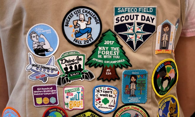 """FILE - In this June 18, 2018, file photo, patches cover the back of a Girl Scout's vest at a demonstration of some of their activities in Seattle. Girl Scouts of the United States of America claim the century-old organization is in a """"highly damaging"""" recruitment war with Boy Scouts of America after the group opened its core services to girls, leading to marketplace confusion and some girls unwittingly joining the Boy Scouts. (AP Photo/Elaine Thompson, File)"""