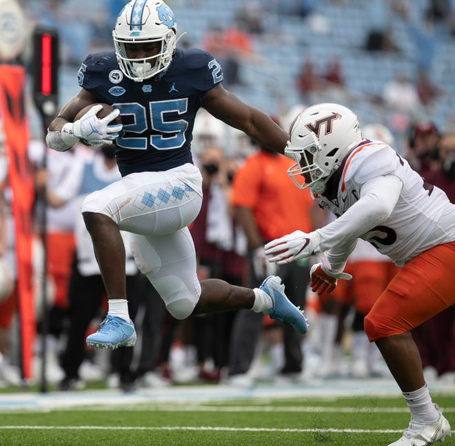 North Carolina's Javonte Williams, left, bounds away from Virginia Tech linebacker Rayshard Ashby on a touchdown run in October.