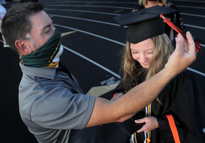 Matt Amerson switches the tassel for his daughter, Ally Amerson, during the Kaukauna High School graduation ceremony on Wednesday, July 29, 2020, at Bank of Kaukauna Stadium in Kaukauna, Wis.