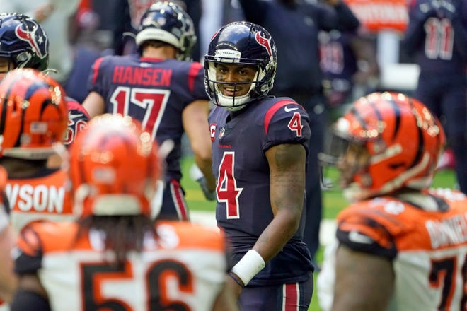 Houston Texans quarterback Deshaun Watson (4) smiles toward Cincinnati Bengals defenders after rushing for a gain during the second half of an NFL football game Sunday, Dec. 27, 2020, in Houston.